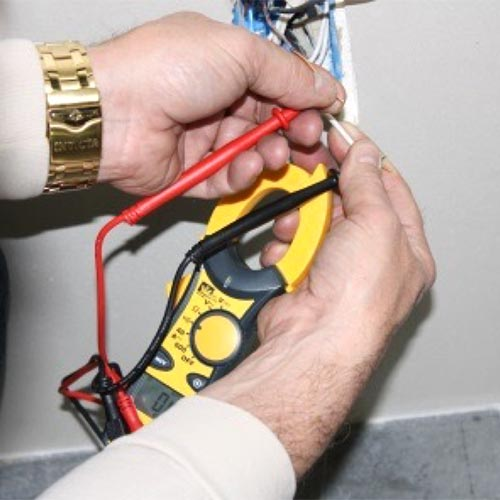 Man checking continuity between two wires with IDEAL clamp meter