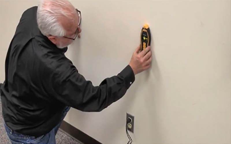 Man tracing wire through wall