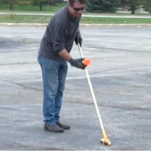 Man tracing wire in through parking lot with circuit tracer and holding cradle.